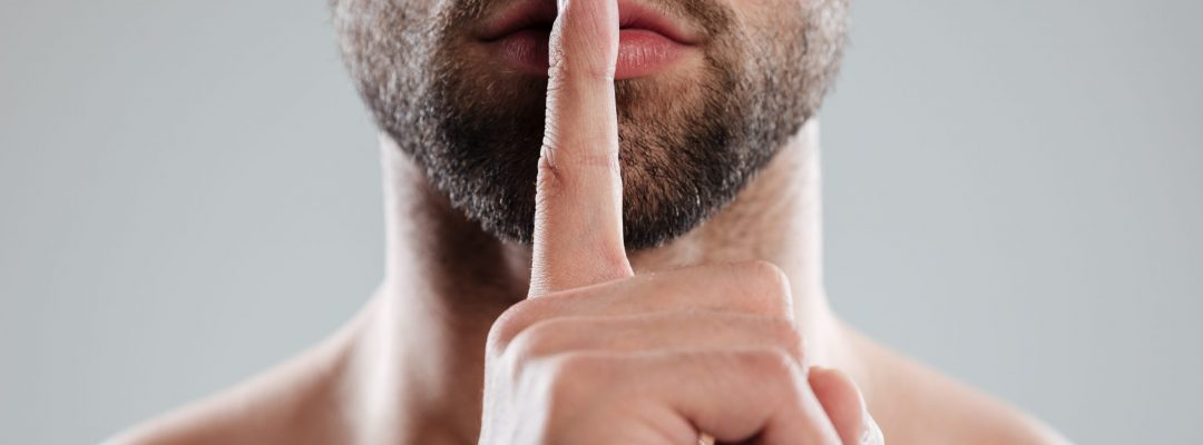 Cropped image of a handsome naked man showing silence gesture with finger over lips isolated over white background